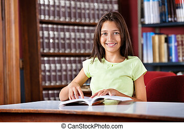 Schoolgirl With Book Sitting At Table In Library
