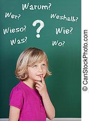 Schoolgirl with doubts in front of the blackboard