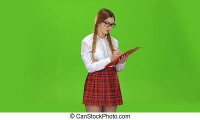 Schoolgirl with glasses writes on white paper. Green screen
