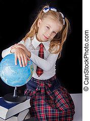 Schoolgirl with globe sitting on black background
