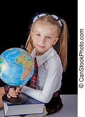 Schoolgirl with globe sitting on black background