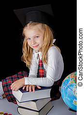 Schoolgirl with hat and globe sitting on black background