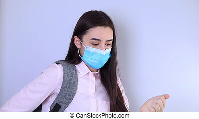 High school girl with backpack with mask on her face using sanitizer. Student girl ready for back to school during the coronavirus pandemic.