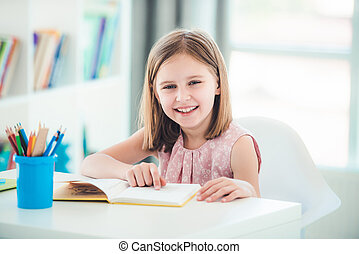 Schoolgirl with textbook sitting at desk