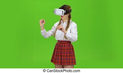 Schoolgirl with virtual reality glasses. Green screen -...