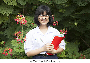 Schoolgirl with wear glasses Smiling and holding a book