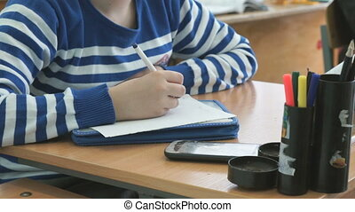 Schoolgirl writes the text on the sheet of paper