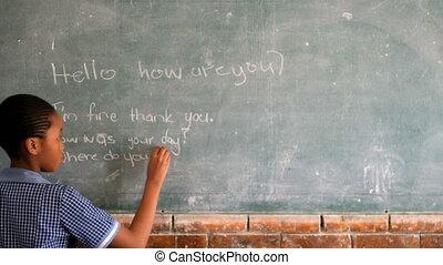 Schoolgirl writing on chalkboard in classroom 4k - ...