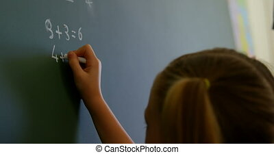 Schoolgirl writing on chalkboard with chalk in classroom at ...
