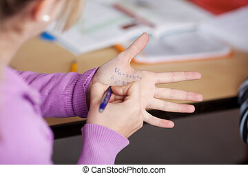 Schoolgirl writing on her hand for cheating in the class...