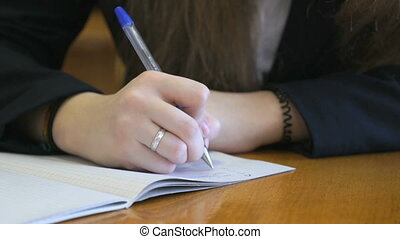 Schoolgirl dressed in a black suit sits at a school desk writing text in exercise book using ballpoint pen. Close-up