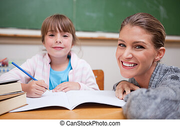 Schoolgirl writing with her teacher in a classroom