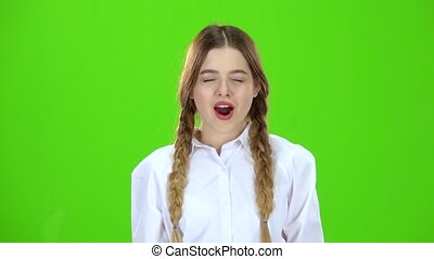 Schoolgirl yawns . Green screen