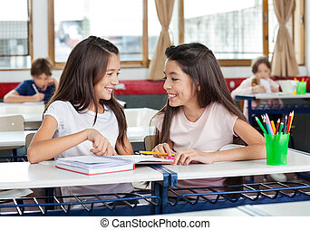 Schoolgirls Looking At Each Other In Classroom - Happy cute...