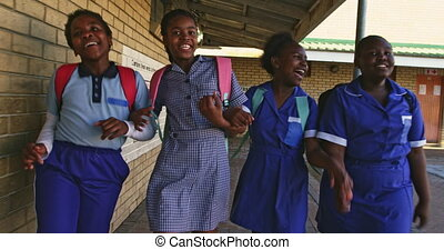 Schoolgirls running in the playground at a township school ...