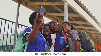 Schoolgirls taking selfies in the playground at a township school 4k