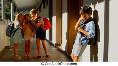 Schoolkids bullying a sad boy in the corridor of elementary ...