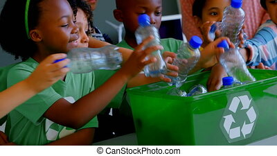 Schoolkids putting bottles in recycle container at desk in ...
