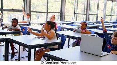 Schoolkids raising hands in the classroom at school 4k