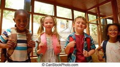 Schoolkids standing together in corridor of elementary ...
