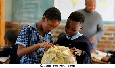 Schoolkids using globe in classroom 4k - Schoolkids using ...