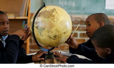 Schoolkids using globe in classroom 4k