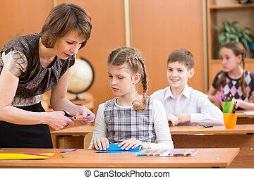 Schoolkids work at labour lesson. Teacher helping pupil.