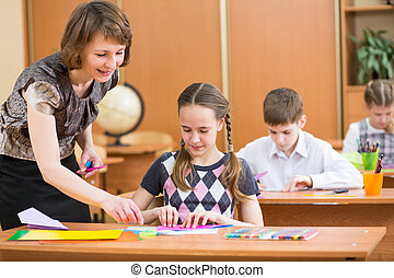 Schoolkids work at lesson. Teacher looking at pupil