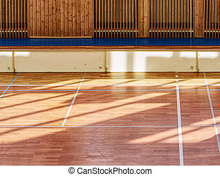 Schooll gym hall with heating system over wooden bars cover