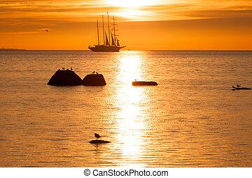Schooner silhouette at sunset in sea