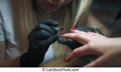 schoonheidspecialist, in, black , handschoenen, houden, client's, hand, en, doen, manicure, in, spijker, salon., specialist, deksels, de, spijker, van, de, klant, door, fixer, in, knapheid salon