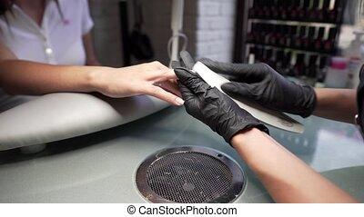 schoonheidspecialist, malen, de, spijker, bar, voor, een, manicure, in, de, beauty, salon., vinger draadnagel, behandeling, het malen, en, polishing., manicure, handen, maken, vrouwlijk, manicure, met, nagelknippers, in, de, spijker, salon.