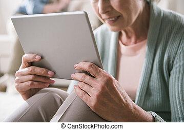 schot knipte, van, oude vrouw, gebruik, digitaal tablet, terwijl, zittende , thuis