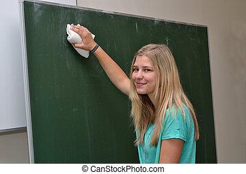 Schuelerin loescht Schultafel - Student erases blackboard