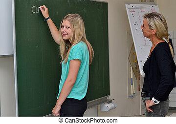 Schuelerin schreibt an der Schultafel - Student writes on...