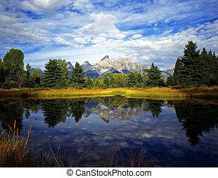 The Teton Range reflecting in the Snake River, at Schwabachers Landing, in Grand Teton National Park, Wyoming.