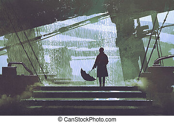 man with umbrella stands under building in rainy day