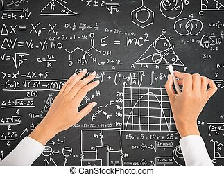Hand writing science and math formulas on chalkboard