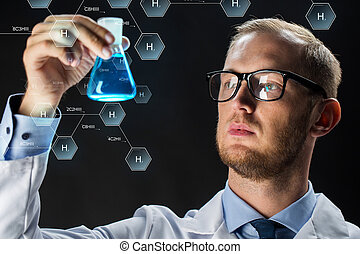 science, chemistry, research and people concept - young scientist holding test flask with chemical over black background