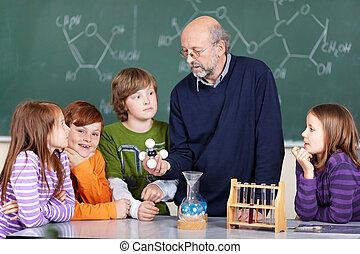 Science class - Portrait of teacher instructing students...