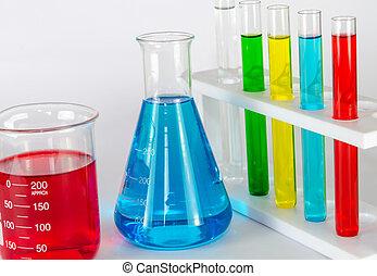 Volumetric laboratory glassware containing colored liquids on table.