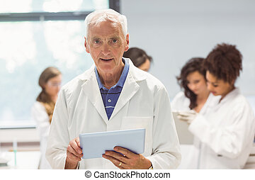 Science lecturer holding tablet pc in lab