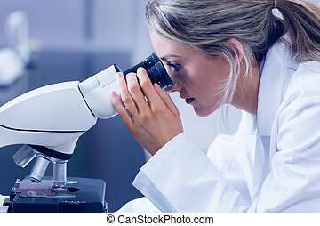 Science student looking through microscope in the lab at the...