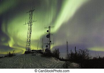 SCientific antennas under night sky with northern lights