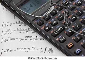 scientific calculator, reading glasses, math book background