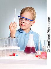 Scientific curiosity - Boy in protective eyeglasses being...