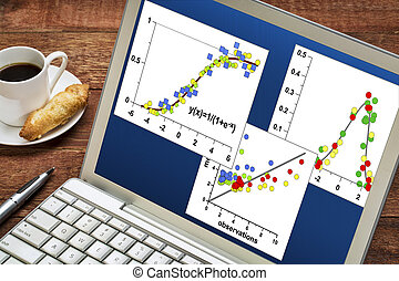 scientific data graphs on a laptop - reviewing and analyzing...