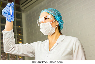 Scientific researcher holding at a liquid solution in the lab.