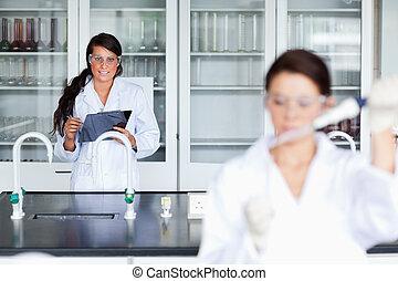 scientifique, femme, presse-papiers, écriture