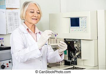 Scientist Analyzing Blood Sample In Laboratory